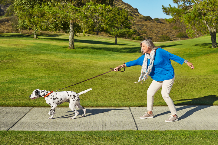 White woman in a park with a dog on a leash pulling her forward